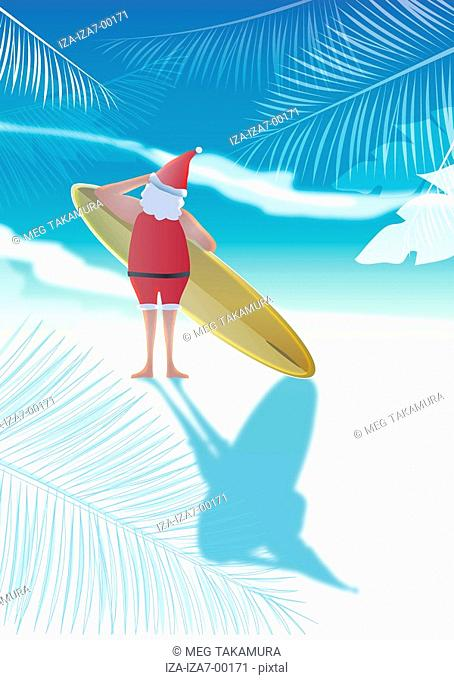 Rear view of a Santa Claus holding surfboard on the beach