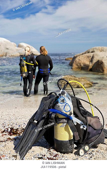Close-up of scuba equipment on beach with divers in ocean in background