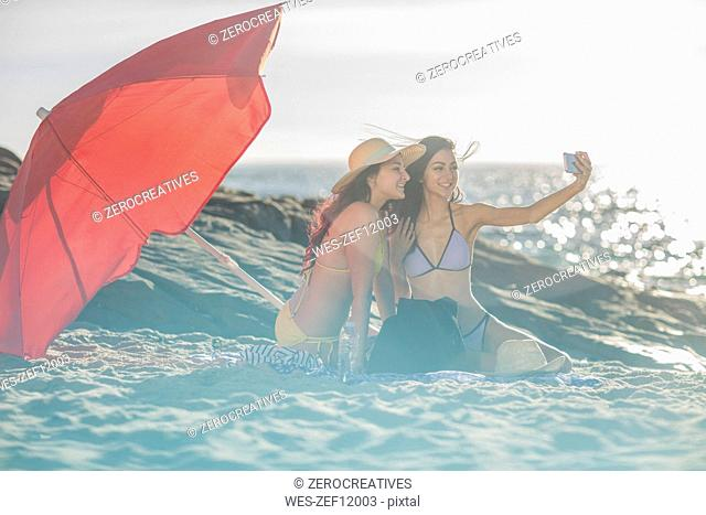 Two young women on the beach taking selfies