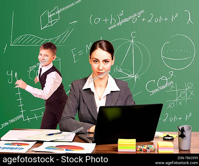 Teacher sitting at the desk and young pupil white on blackboard at classroom