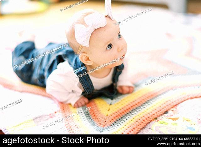 baby girl on a blanket practicing head support during tummy time