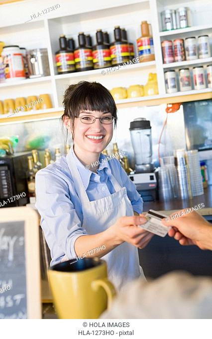 Portrait of a female store clerk receiving a credit card