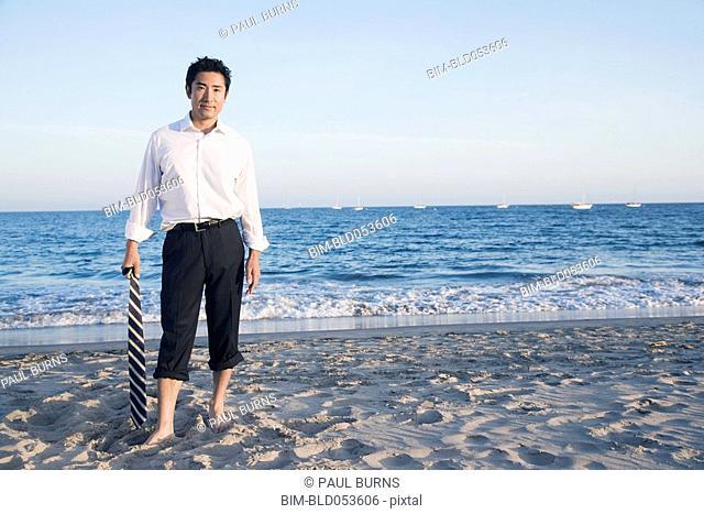 Asian businessman standing on beach
