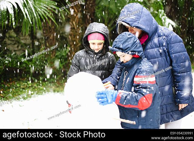 Children build snowman while snowing