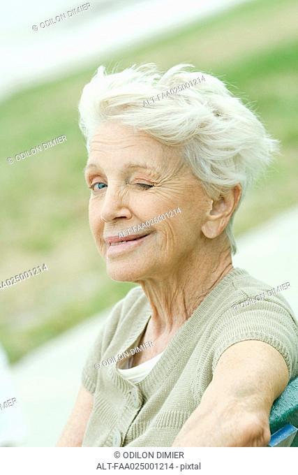 Senior woman winking at camera, portrait