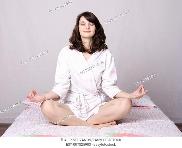 Young beautiful woman waking up in the morning meditating sitting in bed