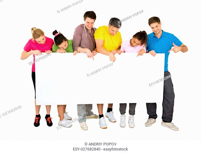 Group Of Smiling People Holding Blank Banner In Front Of A White Background