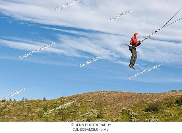 Teenage boy swinging on rope swing