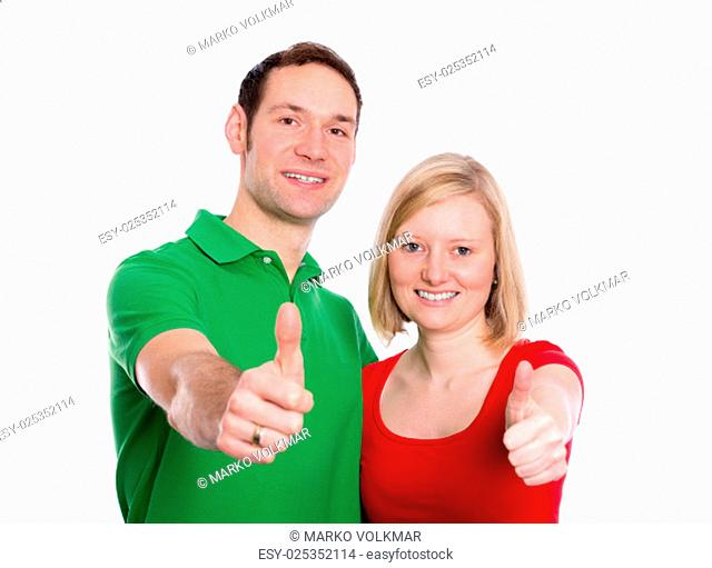 young happy couple in front of white background with hands with thumbs up