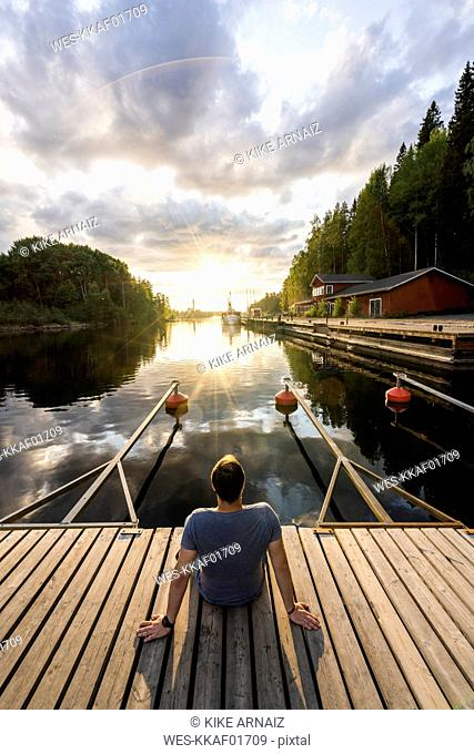 Finland, Kajaani, Man sitting on jetty, watching sunset, rear view