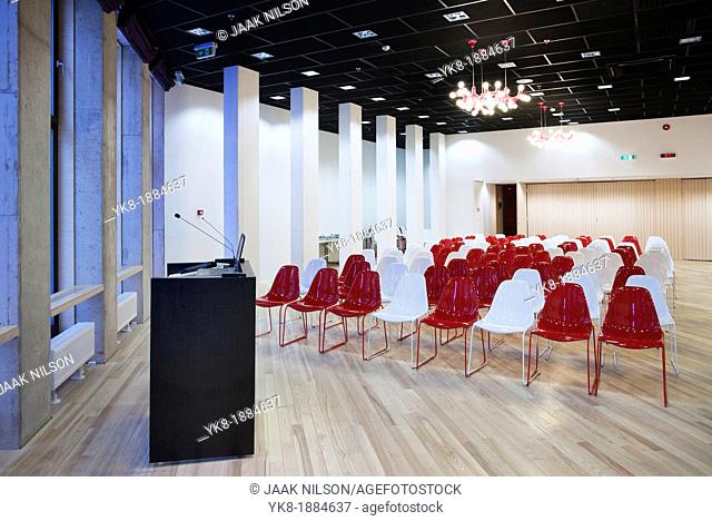 Modern large conference hall with lectern podium and colourful chairs in auditorium of Tartu Health Care College in Estonia
