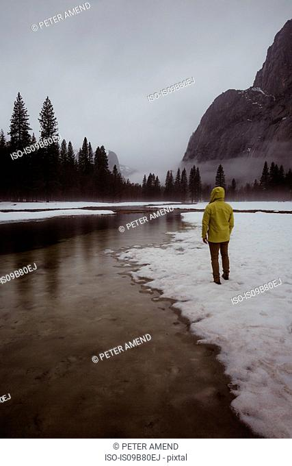 Rear view of male hiker looking out over snow covered landscape and river, Yosemite Village, California, USA