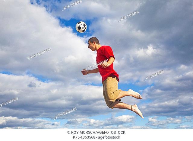 Hitting soccer ball high in the sky