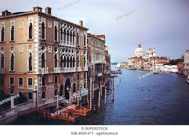 Boats moored at canal with Basilica in the background, Santa Maria Della Salute, Dorsoduro, Grand Canal, Venice, Italy