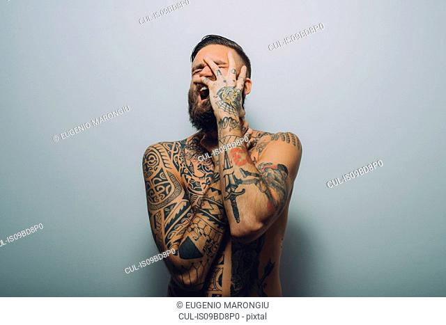 Portrait of young man with beard, covered in tattoos, hand on face, screaming