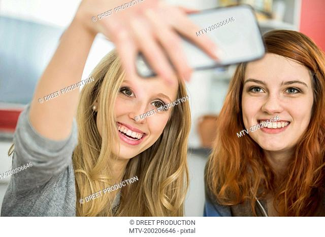 Happy girl friends taking a selfie with smartphone, Munich, Bavaria, Germany