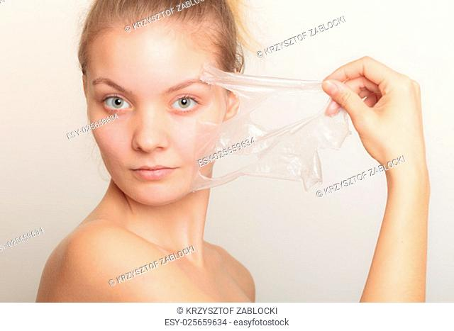 beauty skin care cosmetics and health concept. closeup of a young woman face,girl removing facial peel off mask on gray. peeling