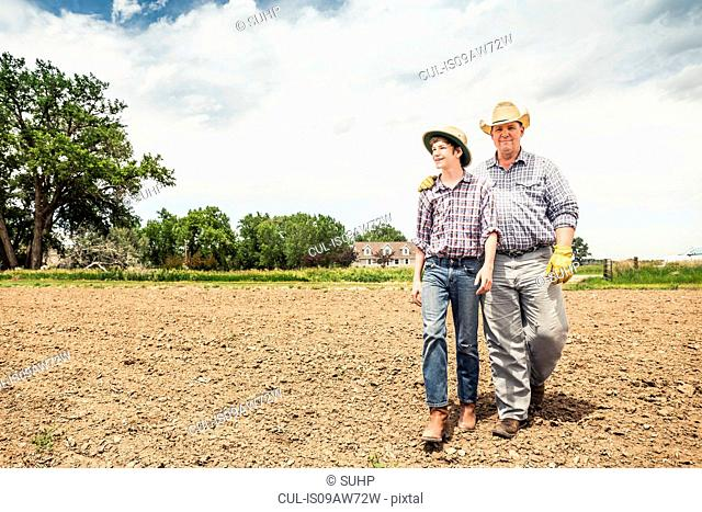 Farmer and teenage grandson walking over ploughed field