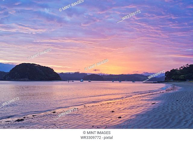 Boats sailing in bay at sunrise, Bay of Islands, Paihia, New Zealand
