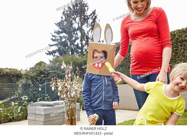 Pregnant mother with boy wearing bunny mask and happy girl in garden