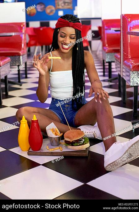 Young woman with braided hairstyle sitting on the floor with her hamburger plate and eating a chip