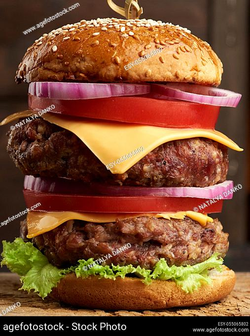 double cheeseburger with tomatoes, onions, barbecue cutlet and sesame bun on an old wooden cutting board. Fast food, close up