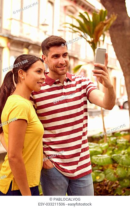 Happy young couple looking at the cell phone smiling while taking a selfie dressed casually in t-shirts with buildings behind them