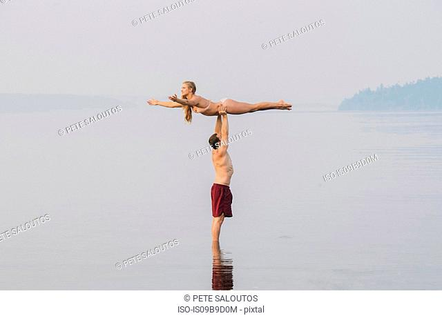 Young couple on beach, man holding woman above head