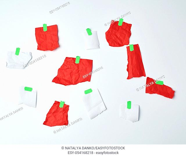 lot of torn red and white pieces of paper glued with green scotch tape on a white background, place for text