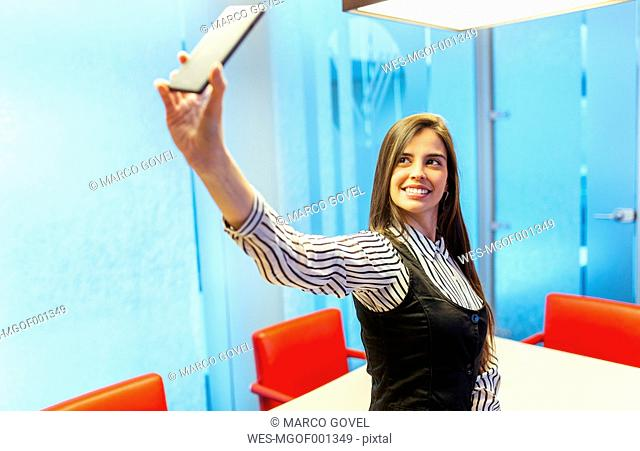 Portrait of smiling businesswoman taking selfie with smartphone in a conference room