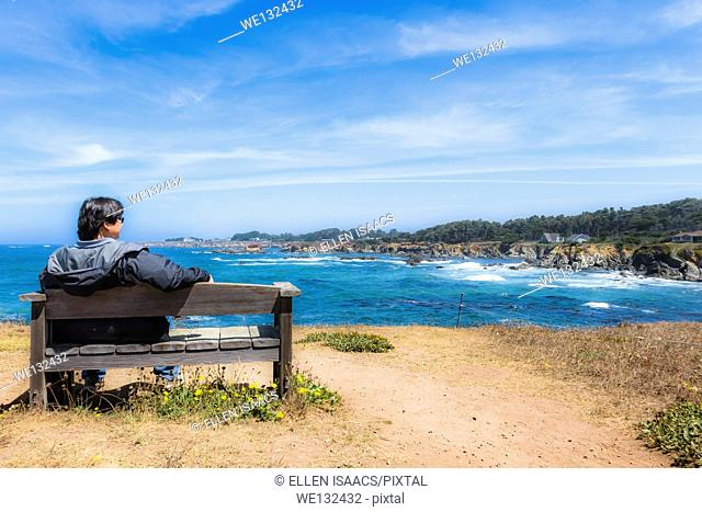 Asian-American man sitting on a bench looking pensive as he looks out at rocky Pacific coastline in Mendocino, California