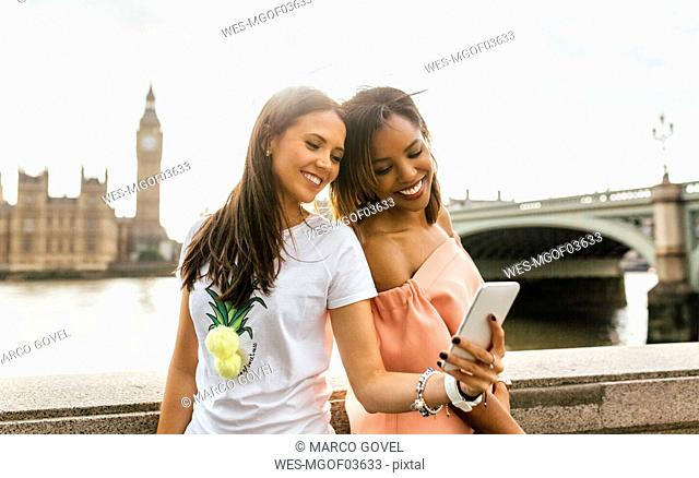 UK, London, two beautiful women taking a selfie near Westminster Bridge