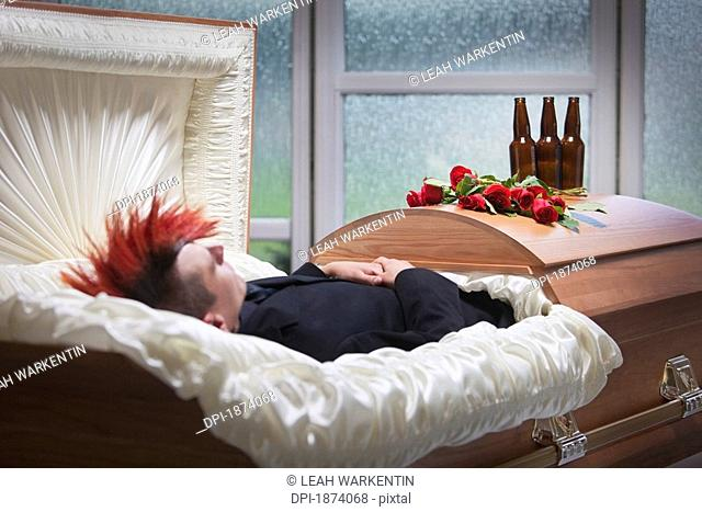 a deceased young man laying in a coffin with beer bottles on top of it