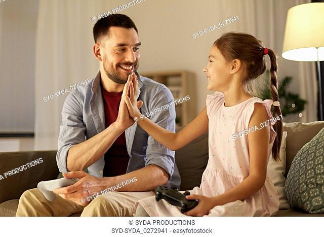 father and daughter playing video game at home