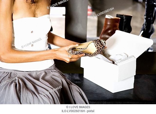 Woman buying high-heeled shoes in a shoe shop