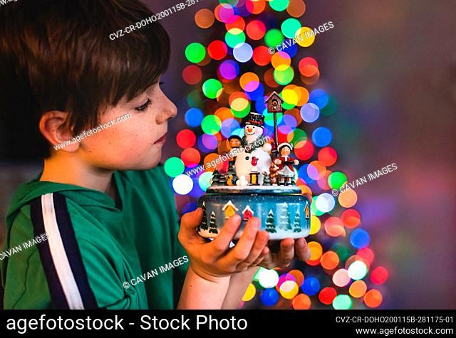 Boy holding Christmas decoration with tree lights in background