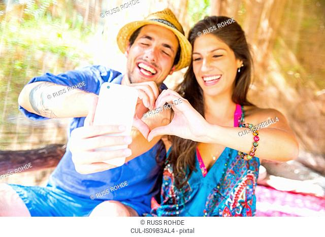 Couple making heart shape with hands taking selfie