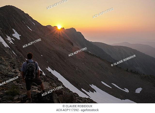 Hiker watching the sunset near the summit of Frosty Mountain in Manning provincial park, British Columbia, Canada