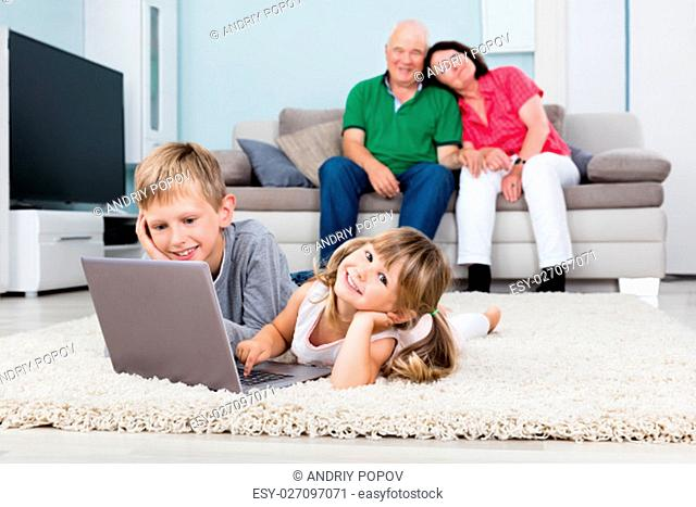 Happy Grandparents Looking At Grandchildren Using Laptop Computer Lying On Carpet At Home