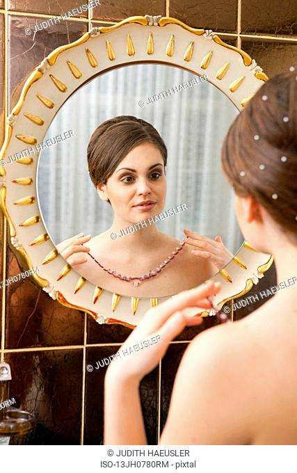 woman with chain in front of mirror