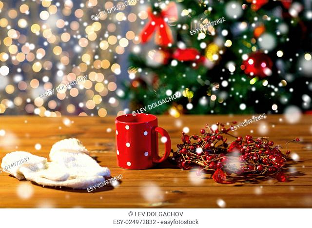 holidays, christmas, winter and drinks concept - close up of tea cup with mittens and christmas decoration on wooden table
