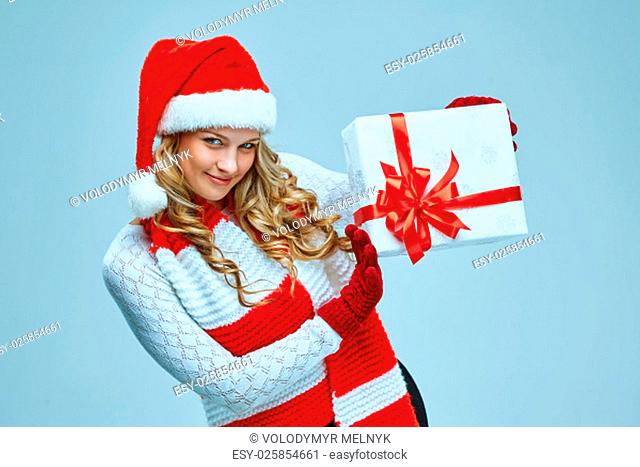 Beautiful young woman in Santa Claus clothes with a gift on a gray background
