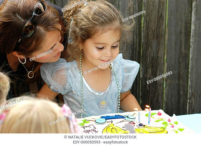 Birthday girl with mother ready to blow out her candles