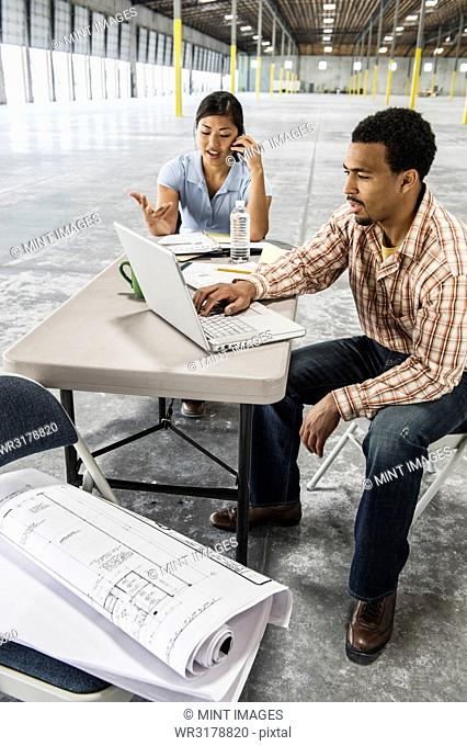 Asian woman and black man sitting at a desk in front of loading dock doors working on plans for new warehouse interior