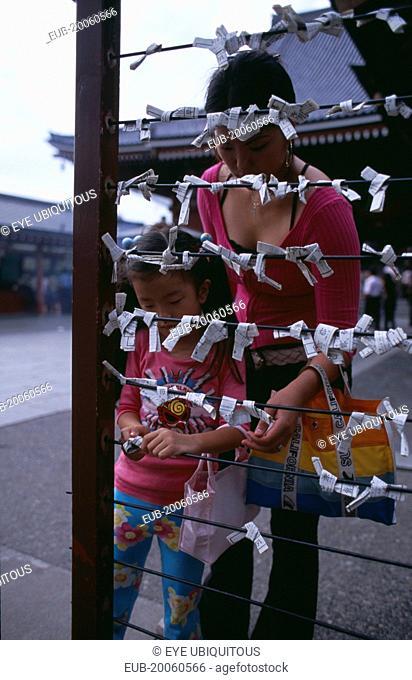 Asakusa. Woman and girl tying Omikuji or Fortune papers at Senso Ji Temple