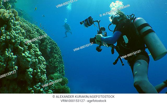 Underwater photographer with a camera swims along the wall of a coral reef, medium shot