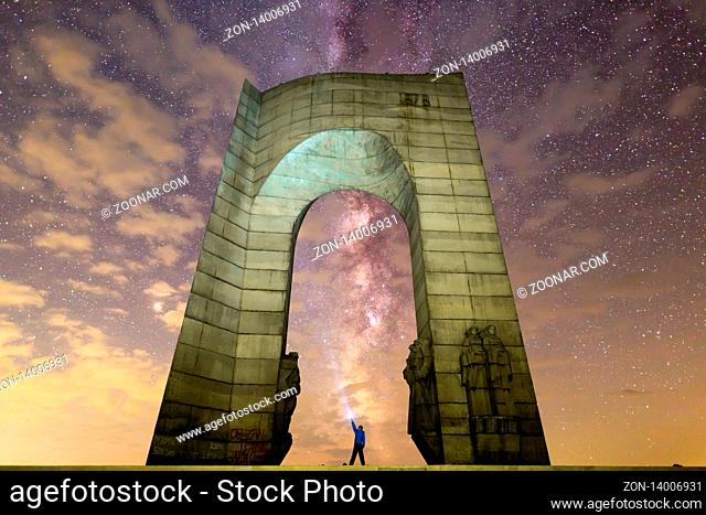 Troyan, Bulgaria - 16 August 2018: A man stands with a flashlight in the base of The Arch of Freedom monument with the Milky Way in the foreground