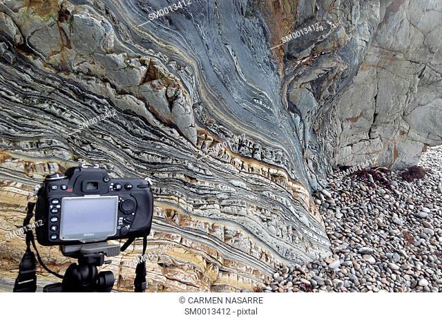 Digital SLR camera mounted on a tripod to photograph rock strata on a beach
