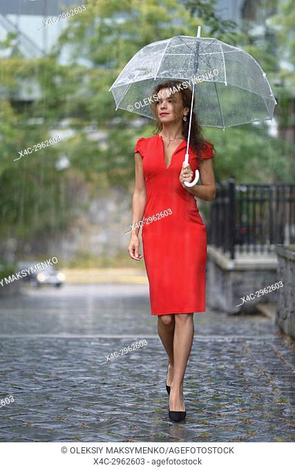 Woman in red elegant dress walking with an umbrella in the rain on a city street