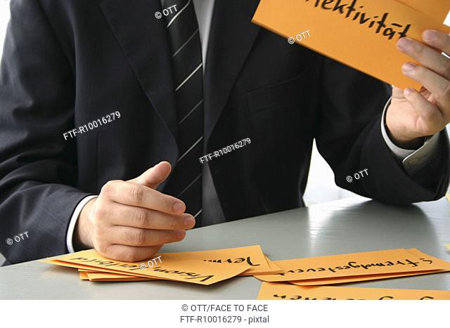 Some named orange papers held by a businessman